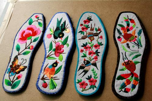 剪贴绣,把各种颜色的布料剪成花,叶,杆,飞虫,小动物等,再绣在面料上.
