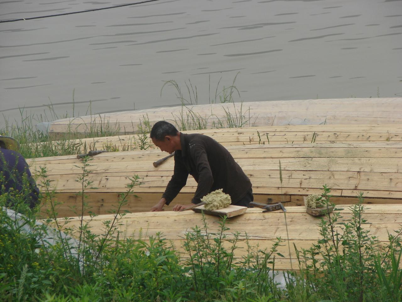 造船工序   整个造船工序主要分九个部分: 1、选料、备料。钉木船要选择天然的老龄杉木,此木材材质结实、有恝性,所造之船吃水浅、浮力大,能载重,轻巧灵敏而且比较坚固耐用。 2、断料、配料。断料配料的尺寸依船体结构而定。船体一般由船底、船邦和横梁组合而成的船头、中舱和船艄三段体,船的大小不一,断料尺寸比较有讲究。 3、破板。圆木断料后,第一步就是破板。从前没有电锯,全靠手工拉锯,先用墨斗和划齿按实际需要的厚度划线、弹线,然后架码拉锯破板。 4、分板。破板后,须用粗、细刨将锯面刨光,再按实际需要的长度、宽度、