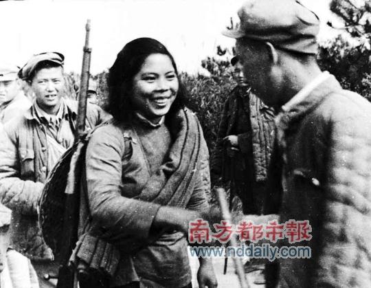 东女游击队长与解放军战士握手.敌后游击队对解放战争的胜利起到